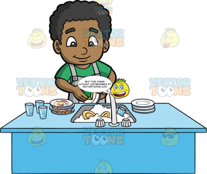 A Happy Black Boy Washing The Dishes After A Meal. A black boy wearing a green shirt and gray apron, stands behind a kitchen sink filled with soapy water and dirty dishes, and uses a sponge to wash a plate