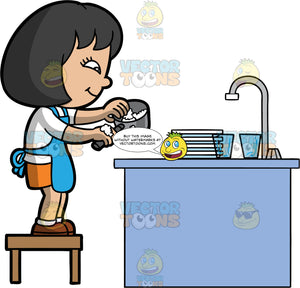 An Asian Girl Washing The Dishes. An Asian girl with black hair, wearing an orange skirt, white shirt, blue apron, and brown shoes, standing on a stool and washing a dirty pot