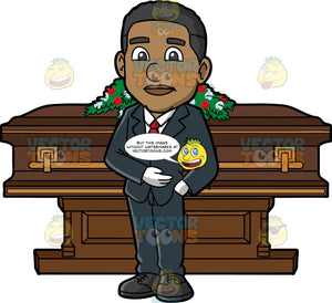 A Black Male Funeral Director Standing In Front Of A Coffin. A black man wearing a midnight blue suit, white dress shirt, black shoes, white gloves, red necktie, stands in front of a brown coffin with gold trimmings and a casket spray of red and white flowers on top