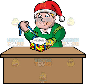 Sam Opening A Christmas Gift. A chubby man wearing a green sweater and a Santa hat, standing behind a table and pulling on a bow wrapped around a gift box