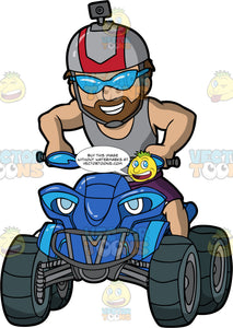 A Macho Man With A Beard Driving A Blue Quad Bike. A muscular man with a beard, wearing purple shorts, grey tank top, a grey helmet with camera on top, grins as he drives around on his blue all terrain vehicle