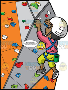 A Black Man Indoor Rock Climbing. A black man wearing yellow pants, a pink shirt, gray rock climbing shoes, a white helmet, and a blue harness, using the hand and foot holds on an artificial rock wall to climb up
