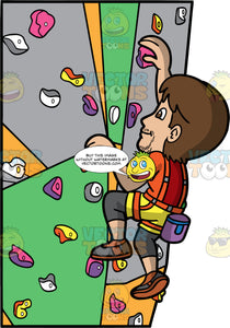 A Man Having Fun Indoor Rock Climbing. A man with brown hair, wearing yellow shorts over gray pants, an orange shirt, gray and brown rock climbing shoes, and an orange harness, climbing up an indoor rock wall
