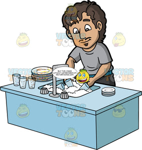 A Man Washing Dishes. A man with brown hair and eyes, wearing dark gray pants, and a gray shirt, standing behind a kitchen sink filled with soapy water, and washing the dirty dishes in the sink and stacked next to the sink
