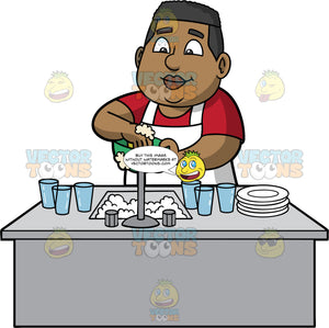 James Washing Up After Dinner. A black man wearing a red t-shirt and a white apron, standing behind a kitchen sink filled with soapy water, and washing a green bowl