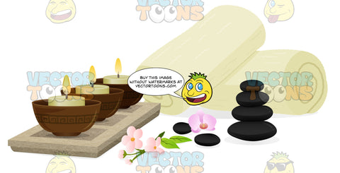 Spa Scene Consisting Of Three Lit Candles, Flowers, A Stack Of Spa Stones And Two Rolled Up Spa Towels