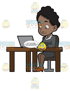 A Black Woman Sitting At Her Desk Using A Laptop Computer