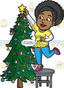 Jackie Putting A Star On Top Of The Christmas Tree. A black woman wearing blue pants, a yellow t-shirt over a long sleeve white shirt, and purple shoes, standing on a stool and reaching up to put a gold star on top of the Christmas tree