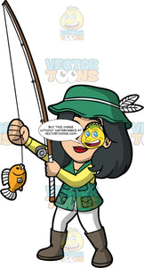 Lynn Admiring The Fish She Caught. An Asian woman wearing white pants, a green vest over a yellow shirt, brown boots, and a green hat, holding a fishing rod and looking at the little fish she caught