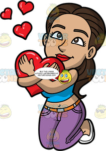 Isbella On Her Knees Hugging Big Heart. A Hispanic woman with dark brown hair and eyes, wearing purple pants, a blue crop top, and white shoes, kneeling down and hugging a big heart and she stares up at someone