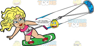 A Woman Strapped Into A Green Kiteboard Hangs On As She Is Pulled Across The Water. A woman with blonde curly hair, wearing a pink bathing suit, hangs onto a bar attached to a blue power kite as the wind pulls her along the water on her green kiteboard