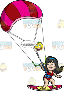 A Happy Woman Propels Across The Water On Her Kiteboard. A woman wearing a red bathing suit and strapped onto a red and yellow kiteboar, holds onto a bar attached to a striped power kite as she surfs across the water