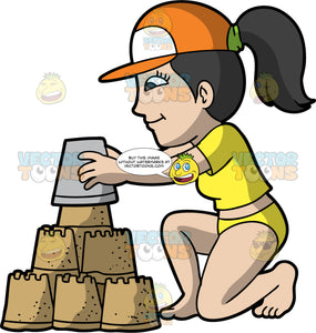 A Woman Building A Three Tiered Sandcastle. A woman with dark brown hair tied in a ponytail, wearing a yellow two piece bathing suit, and an orange baseball cap, kneels down to put a bucket of sand on top of the sandcastle she is building