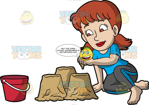 A Woman Adding Sand To Her Sandcastle. A woman with reddish brown hair and brown eyes, wearing black pants and a blue t-shirt, sits in the sand and adds sand to the three small mounds of sand she has made using the red bucket sitting near her