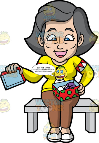 Mary Opening A Gift Box. An older woman with gray hair, wearing brown pants, a yellow sweater with a snowman on it, and white shoes, sitting on a bench and opening a Christmas present