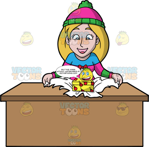Stacey Unwrapping A Christmas Present. A woman with dark blonde hair, wearing a pink, blue and green sweater, and a green and pink hat, standing behind a table and unwrapping a Christmas gift