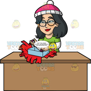 Lynn Opening A Christmas Gift. An Asian woman wearing a green t-shirt over a long sleeve white shirt, pink and white hat, and round eyeglasses, standing behind a table and opening a Christmas present