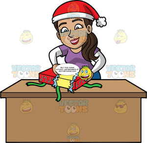 Isabella Unwrapping A Christmas Present. A Hispanic woman wearing a purple t-shirt over a long sleeve white shirt, standing behind a table and opening a Christmas gift wrapped in paper with candy canes on it