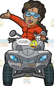 An Indian Woman Driving A Grey ATV. An Indian woman with dark brown hair, wearing an orange track suit, and clear safety glasses, sits on a grey quad bike and holds the handlebar with one hand while she raises her other hand in the air