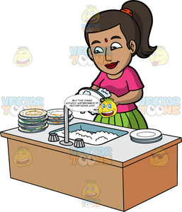 An Indian Woman Washing A Stack Of Dirty Plates. An Indian woman with dark brown hair tied up in a ponytail, wearing a green skirt, and a pink shirt, standing behind a sink filled with soapy water and washing a pile of dirty dishes
