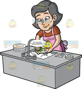 Mary Washing The Dishes After Dinner. An older woman wearing a brown t-shirt and a pink apron, standing behind the kitchen sink washing the dishes