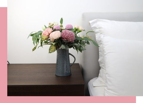 flowers in vase on bedside table