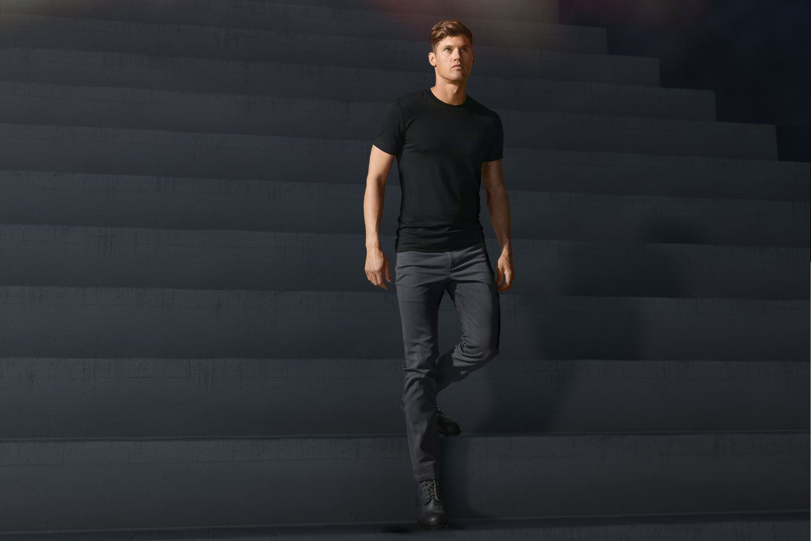 John Paul, center front, wearing Charcoal Slim Dungarees, descending steps. Model is  6' tall, weighs 165 lbs and is wearing Size 31. Model is also wearing our Ultrafine Merino Cut One T-Shirt in Black and a pair of Red Wing Iron Ranger boots.