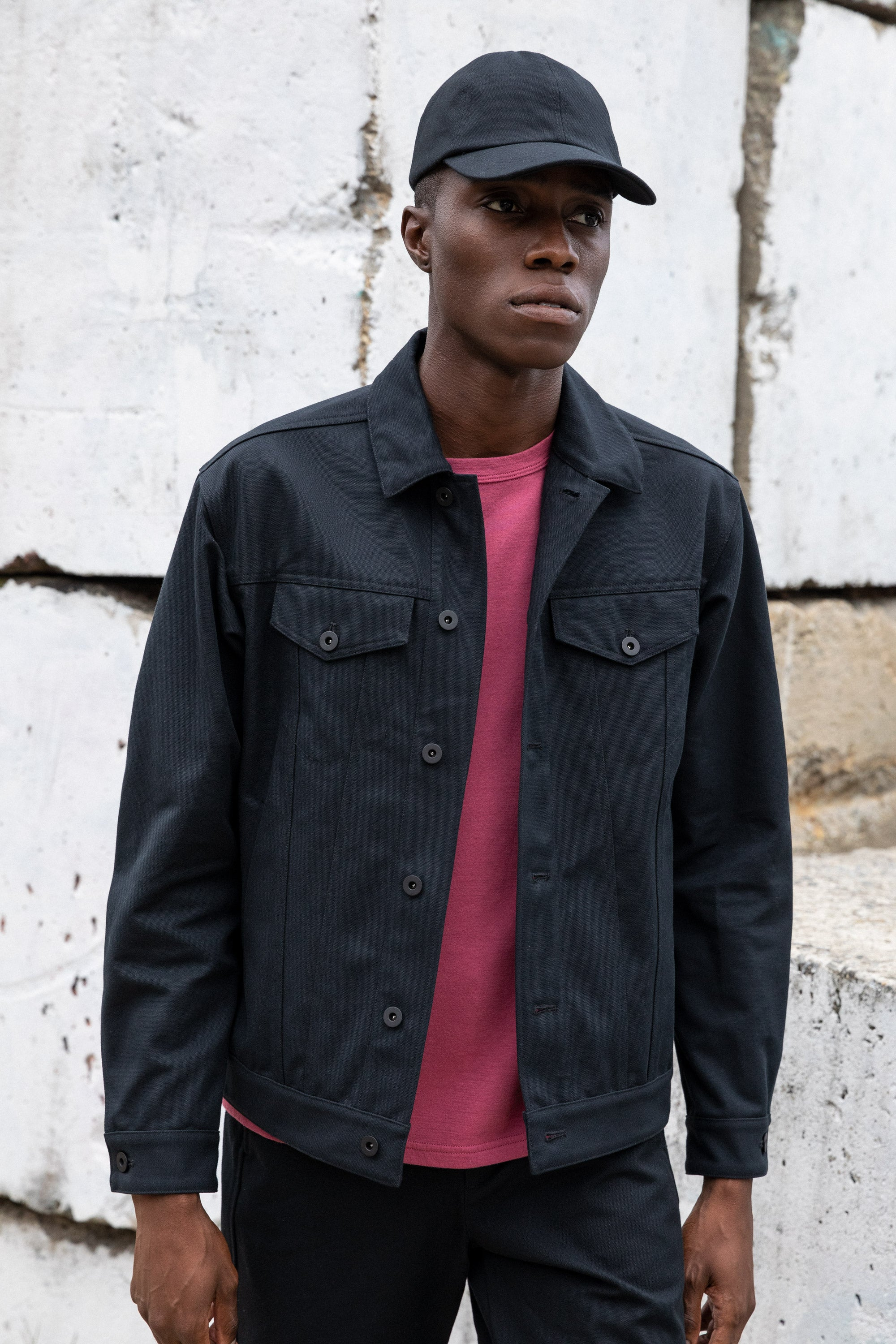 Edem wearing the  Experiment 249 - Duckcloth Shank Jacket in Black along with the Cottonweight Cut Two T-Shirt in GD Dry Rose and the Duckcap in Black