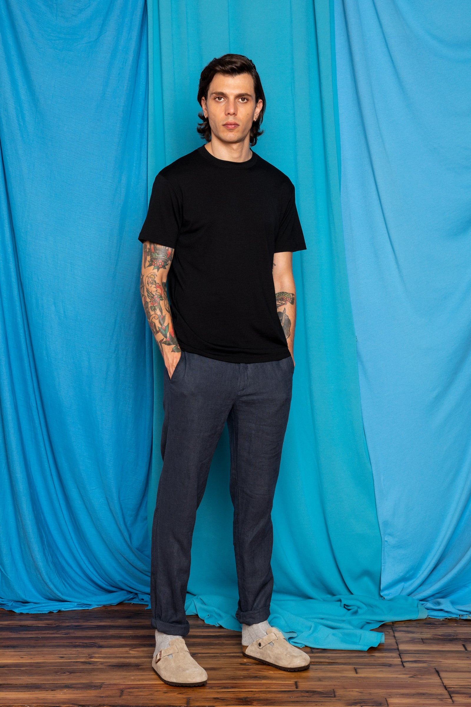 Daniele in the Black Ultrafine Merino Cut Two T-Shirt and Ramiefall Pants , angled front view, hands in pockets