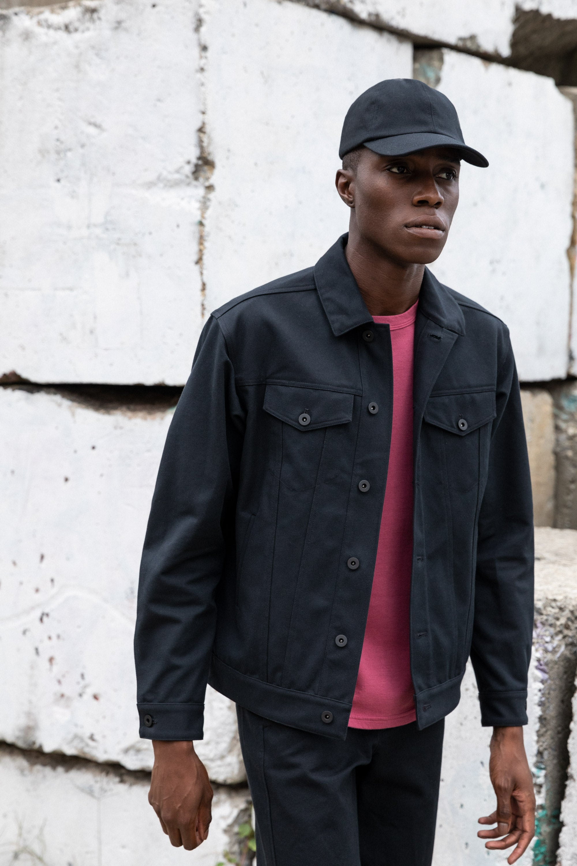 Edem walking away from concrete wall while wearing the Experiment 249 - Duckcloth Shank Jacket