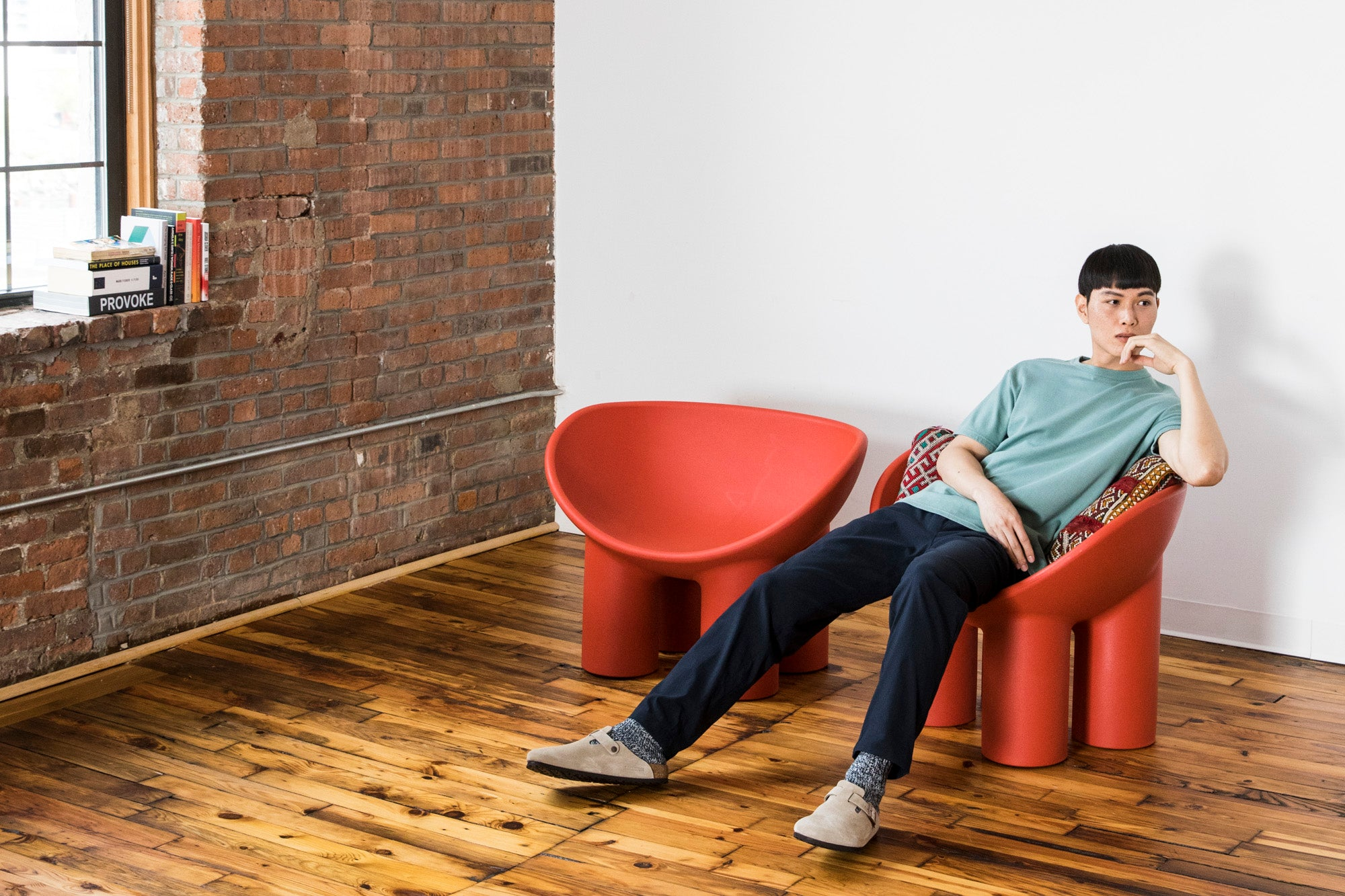 Pace in the F.Cloth Yes Pants in Dark Navy and Cottonweight Cut Two T-Shirt in Sage, sitting on a red chair