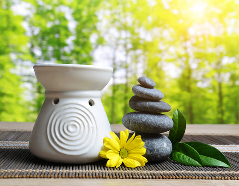essential oil burner with zen rocks and flower and trees in background