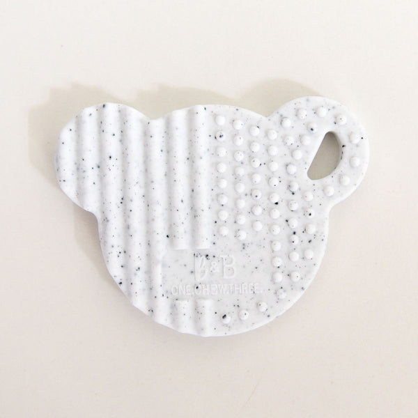 This white speckled, bear head shaped baby teether is a great gift for new mums. With a smooth back and a textured front it is perfect for little gums.