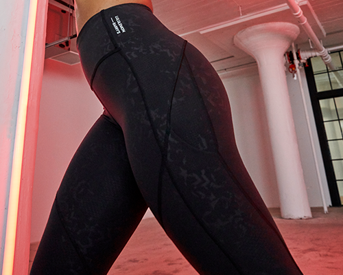 female model leaning forward in black lululemon and barry's bootcamp athletic leggings