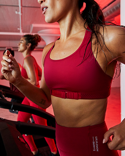 female barry's bootcamp participant running on treadmill in matching red lululemon and barry's sports bra and athletic leggings
