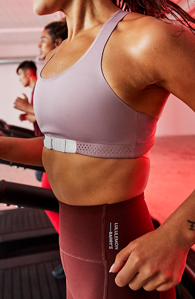 female barry's bootcamp participant running on treadmill in mauve lululemon and barry's sports bra and maroon athletic leggings