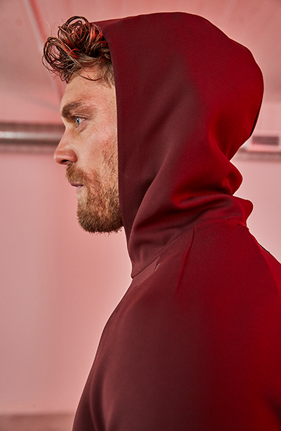 male barry's bootcamp participant looking forward in dark red hooded sweatshirt with hood up