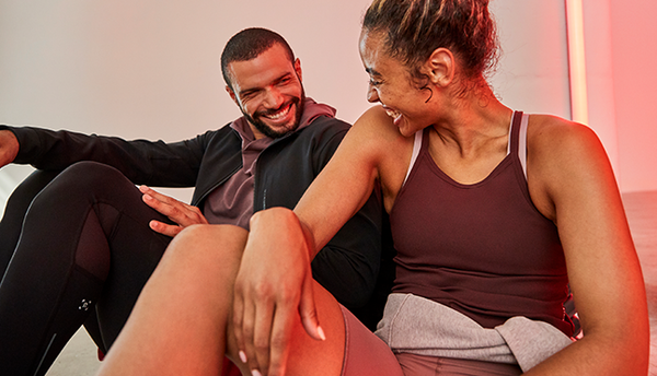 girl in maroon athletic tank top laughing with hand on knee while sitting next to laughing guy in grey sweatshirt and black jacket and sweat pants