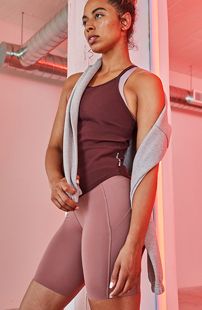 Female barry's bootcamp participant leaning against wall in maroon tank top and mauve athletic shorts and grey sweatshirt