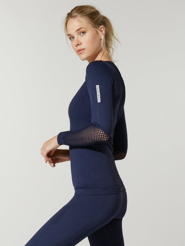 side view of model in navy blue Alala seamless longsleeve top with mesh details on forearms and shoulders