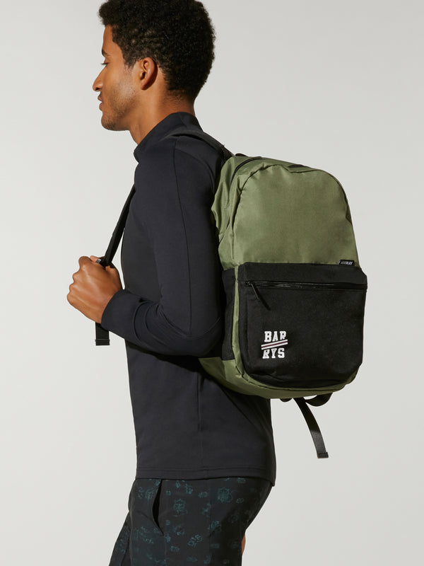 side view of man in black outfit wearing olive and black ace backpack