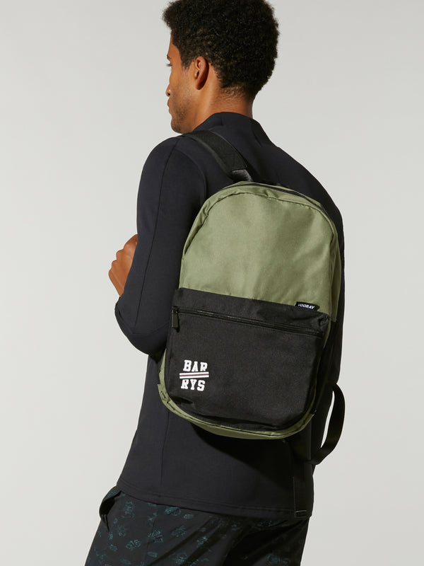 Man in black outfit wearing olive and black ace backpack