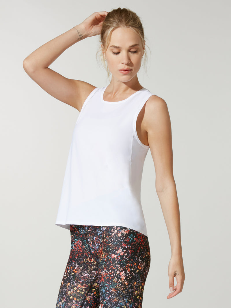 front view of model in white muscle tank top and dark printed leggings