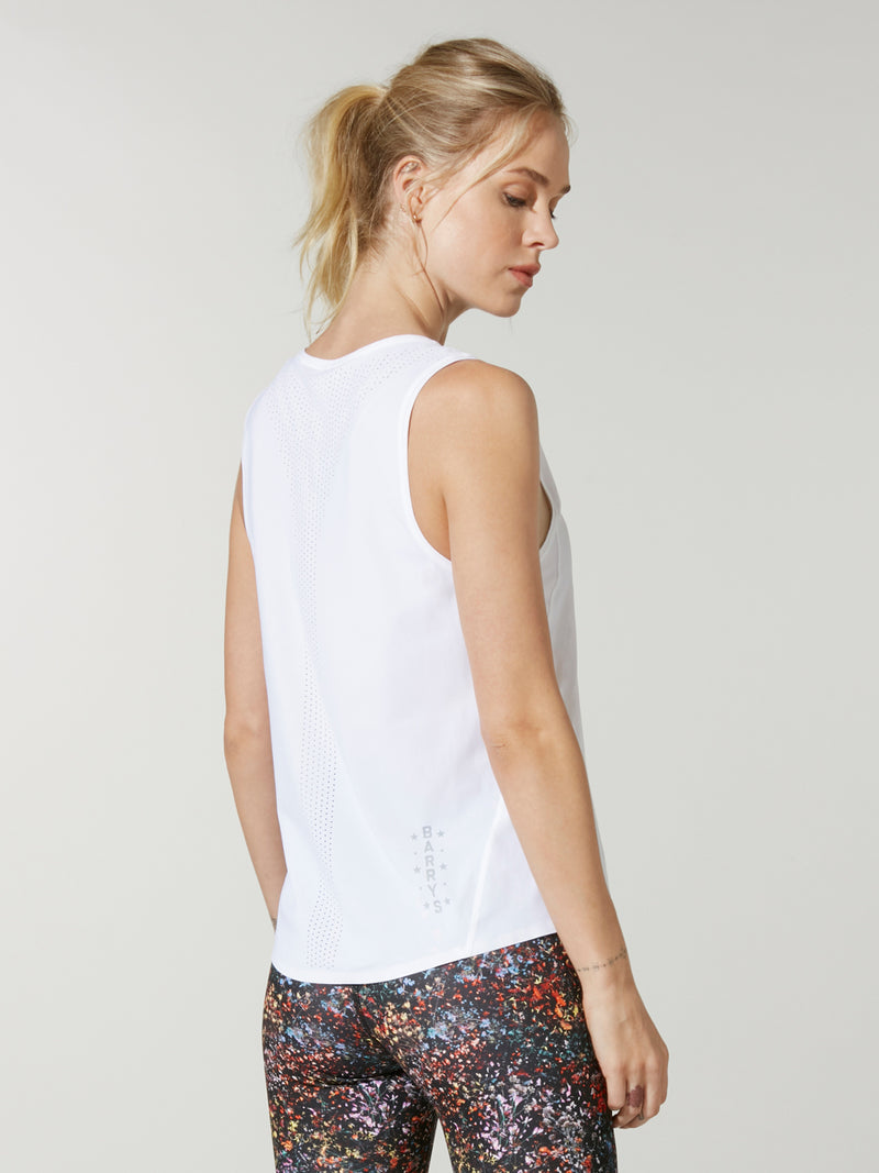 back view of model in white muscle tank top and dark printed leggings