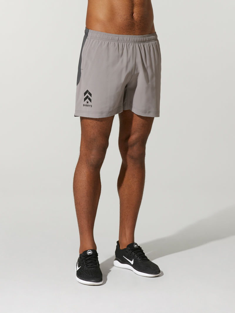 Front shot of model wearing Grey ENDEAVOR X BARRY'S RUN SHORTs with logo on the right side