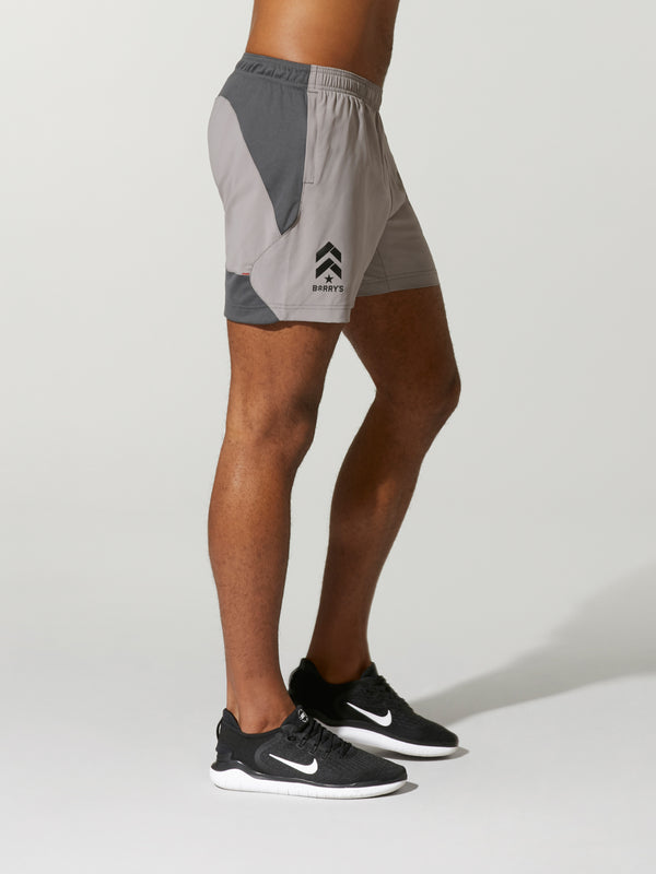 Side shot of model wearing Grey ENDEAVOR X BARRY'S RUN SHORTs with logo on the right side
