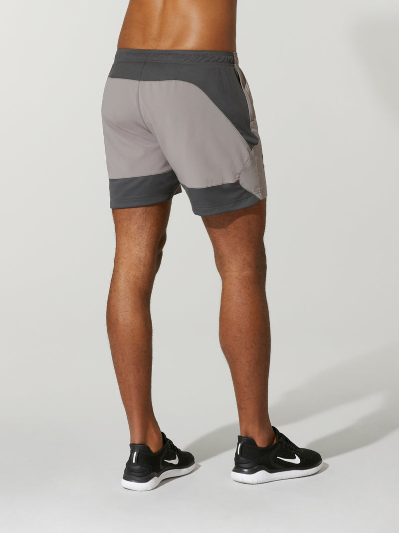 back shot of model wearing Grey ENDEAVOR X BARRY'S RUN SHORTs with logo on the right side