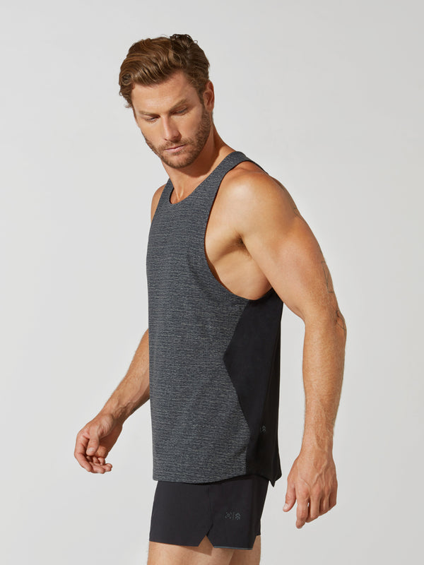 side view of male model in heather grey tank top and matching dark grey athletic shorts