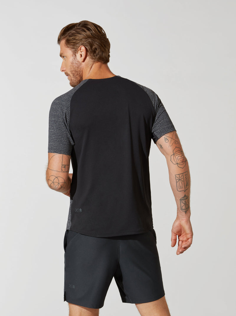 back view of male model in grey t-shirt with black back panel and matching grey athletic shorts