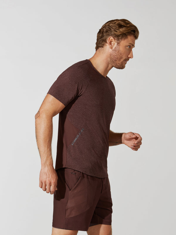 "side view of male model in maroon t-shirt with ""stronger as one"" written on side and matching athletic shorts"